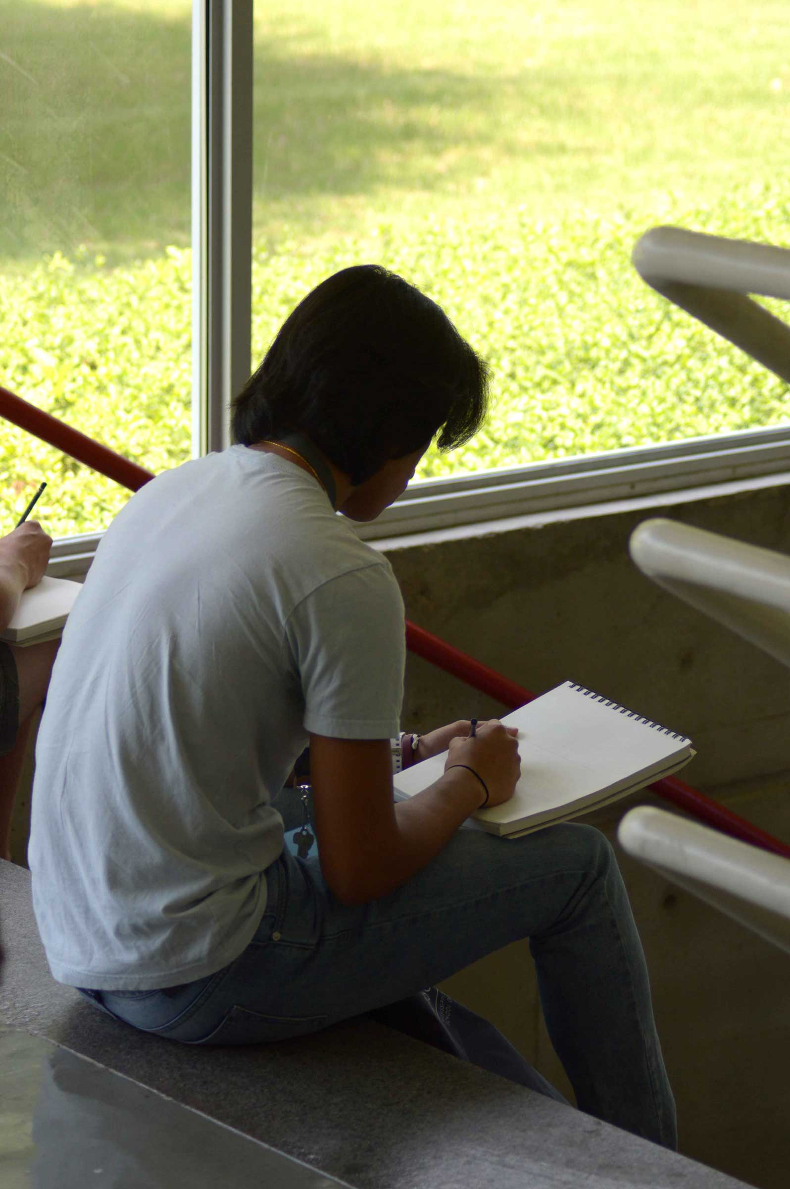 Student sitting on stairs drawing