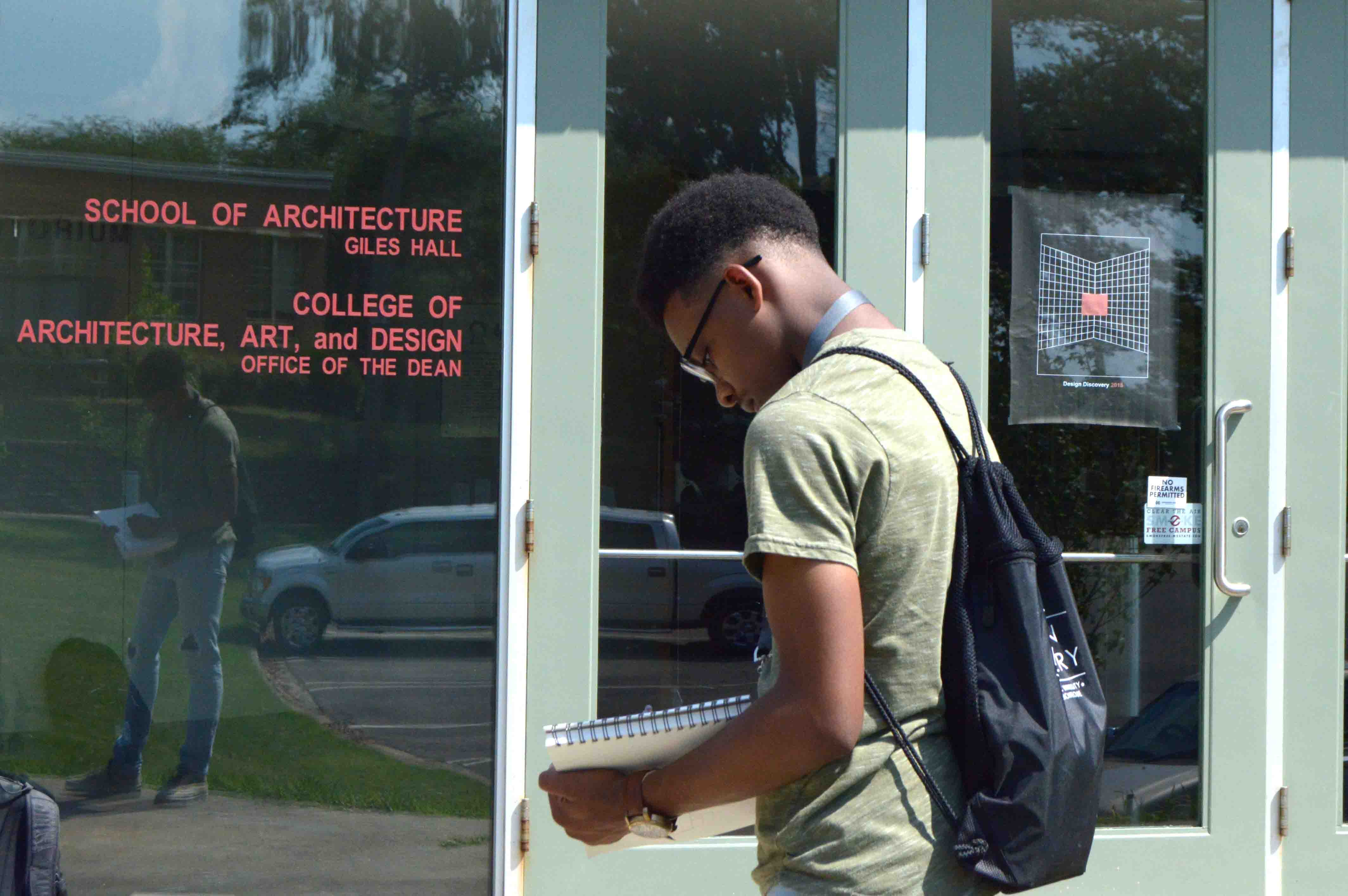 student outside building drawing