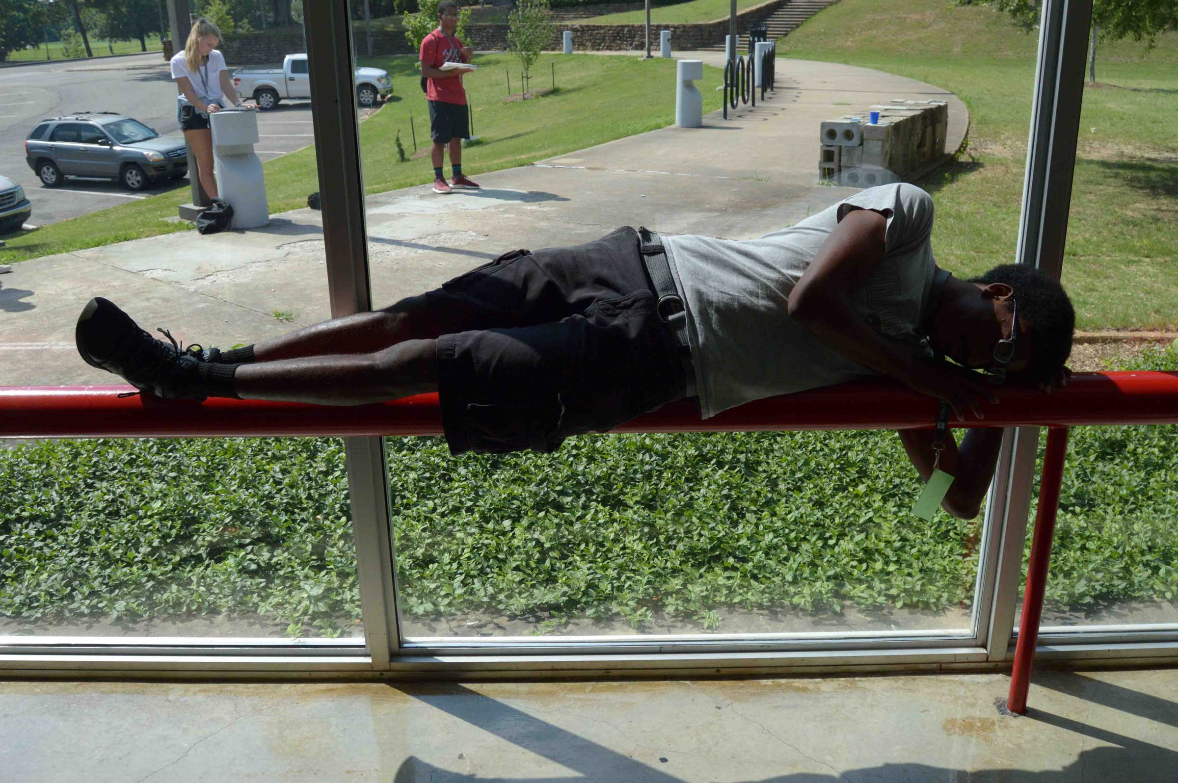 student posing on railing for other students to draw
