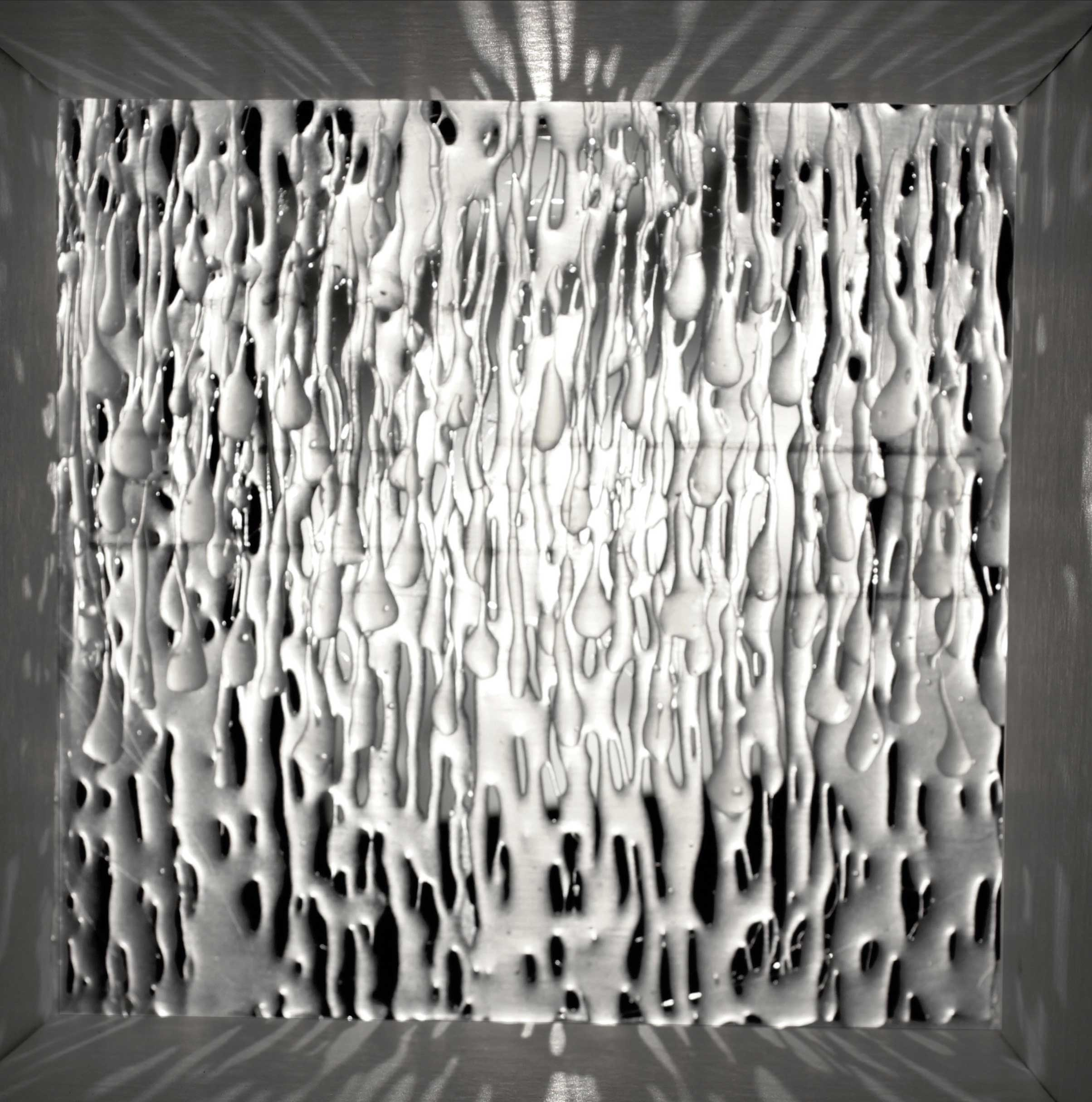 Avery Harmon: Cenotaph Memorial. Black and white image done in a lightbox. The student used foam core and hot glue to create a unique image that looks like water dripping.