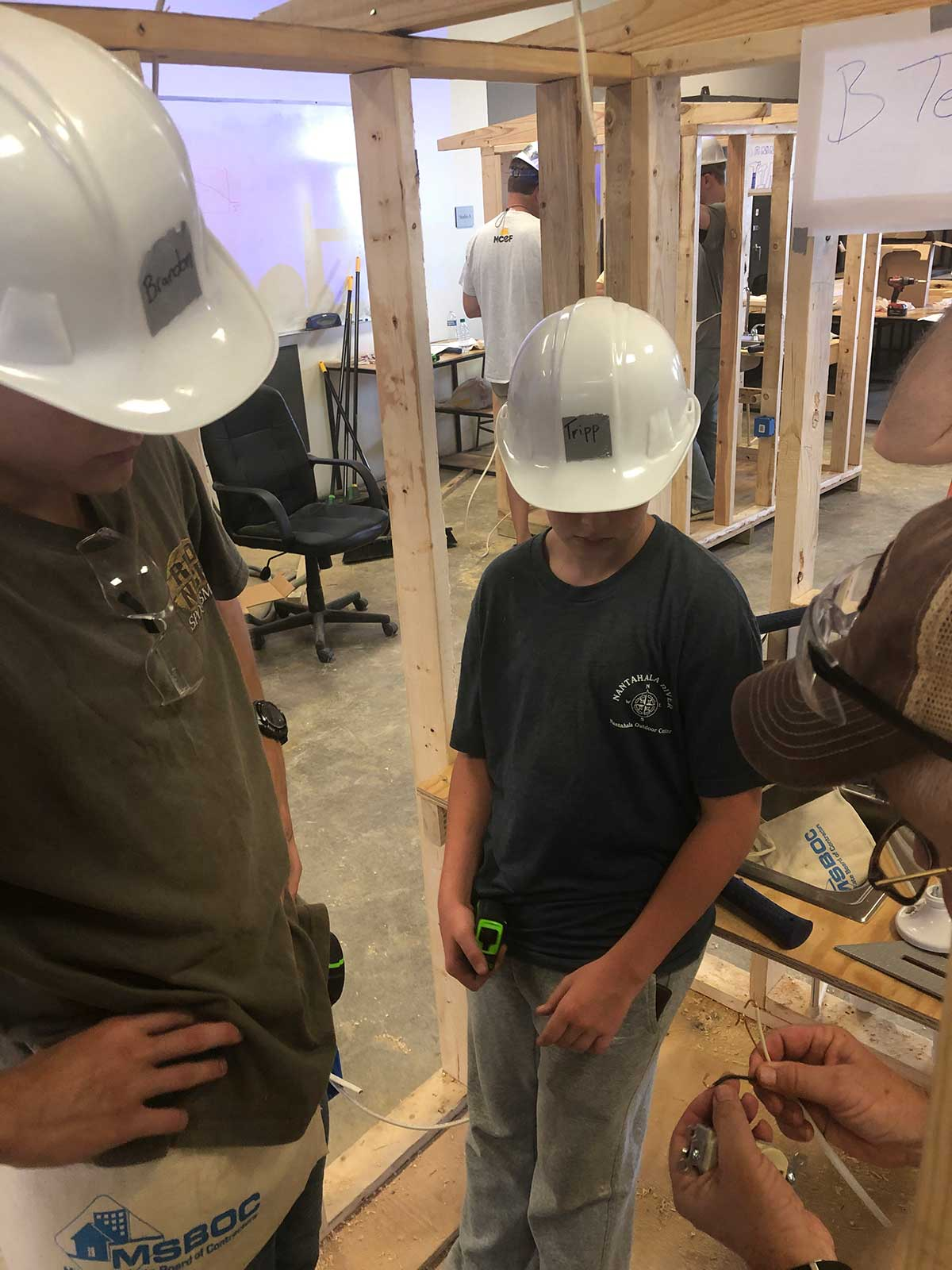 campers look on as construction professional works with wiring