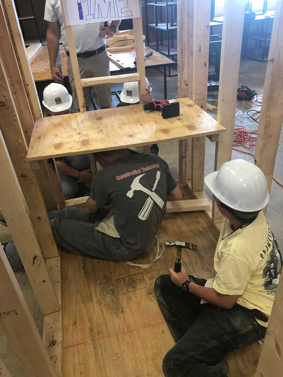 campers work to add wiring to shooting house