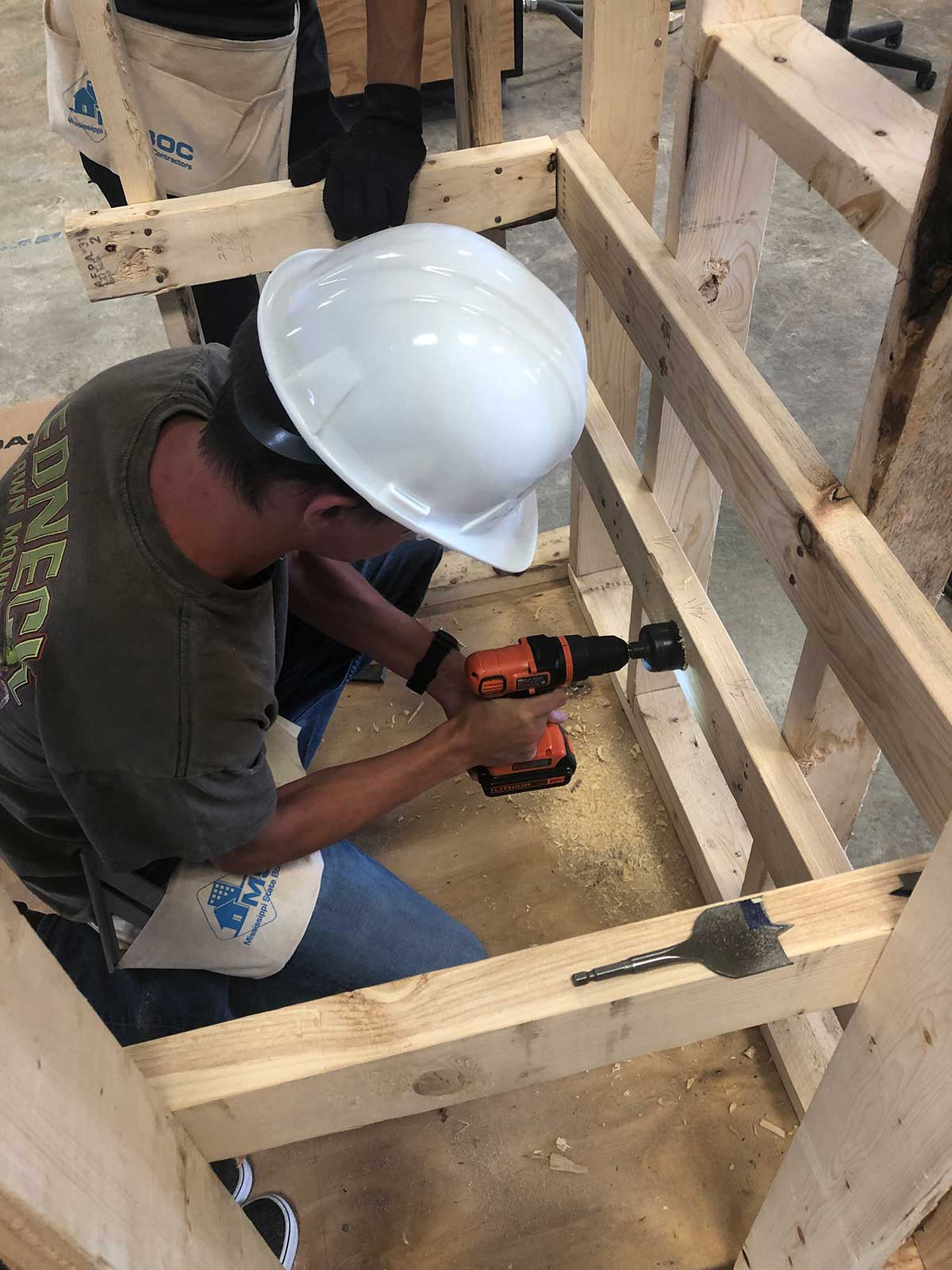 construction professional drills a hole in shooting house interior wood