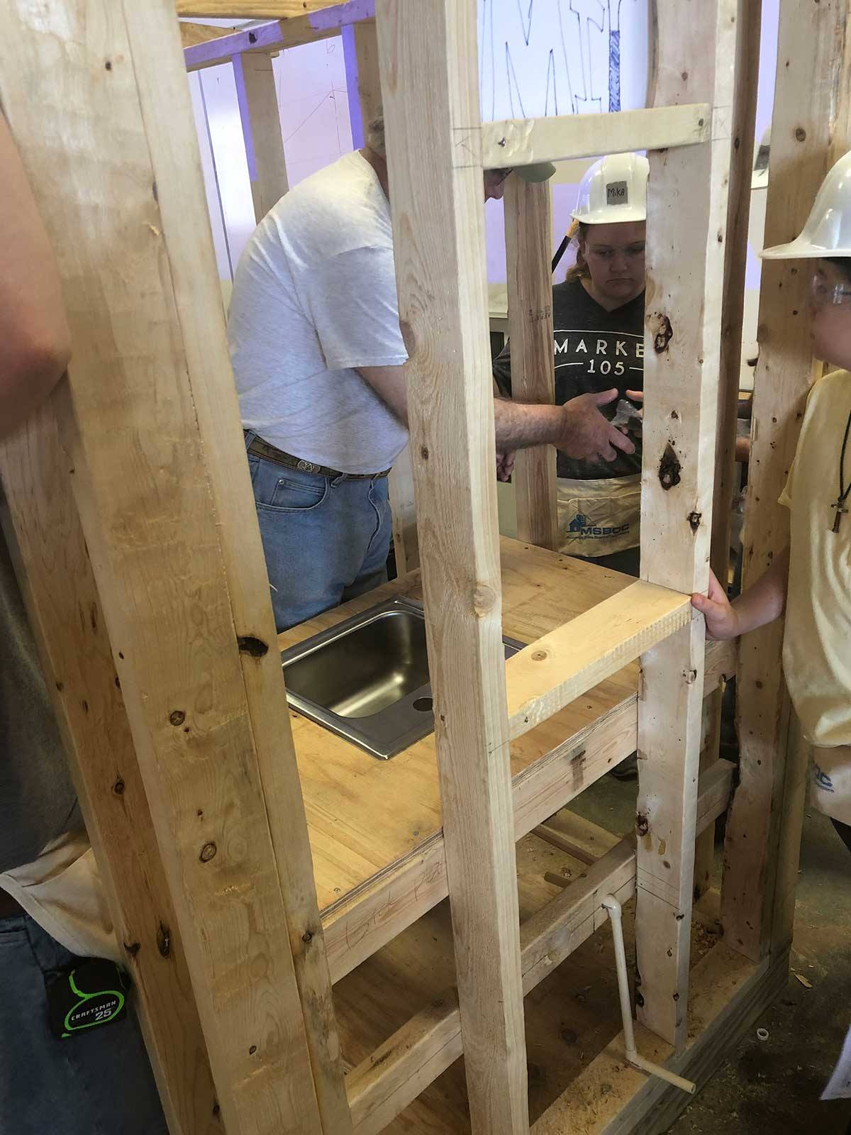 students work near sink of their shooting house with a construction professional