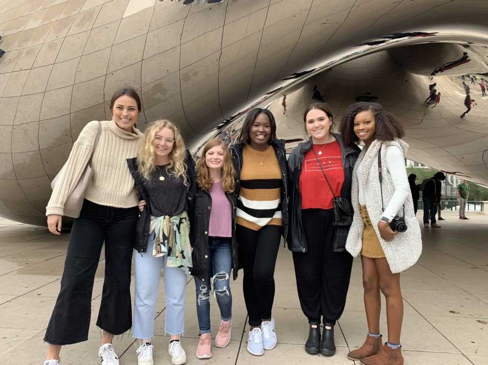 students pose in front of The Bean statue in Chicago
