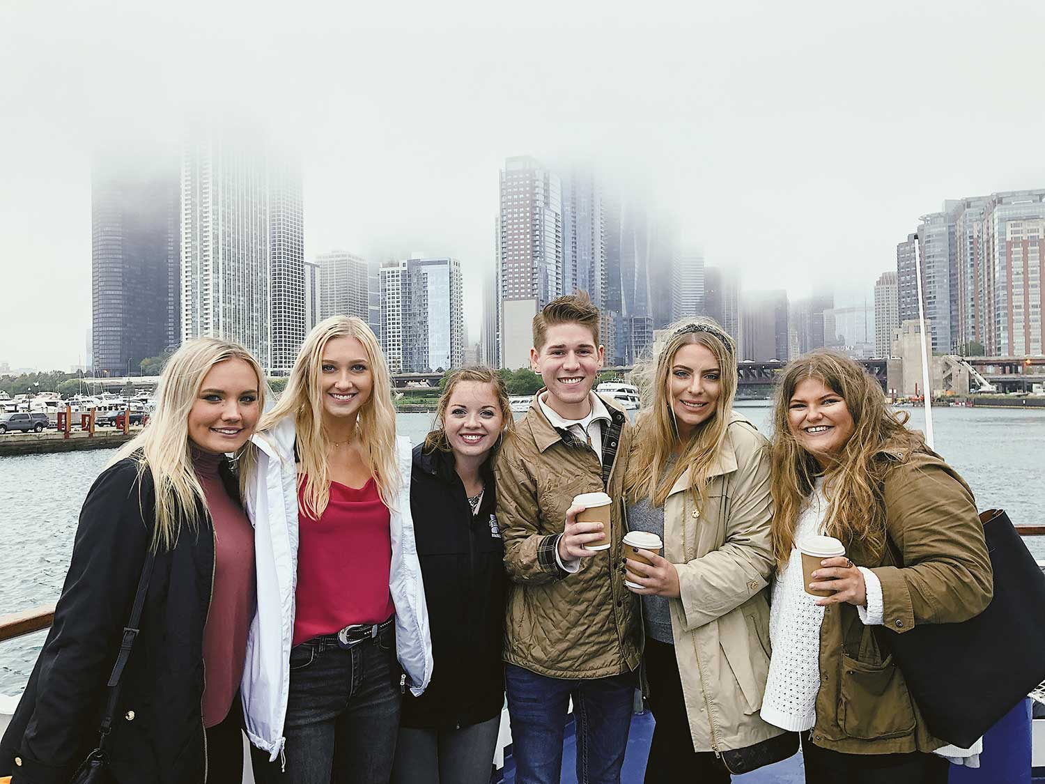 a group of students pose in front of Chicago skyline