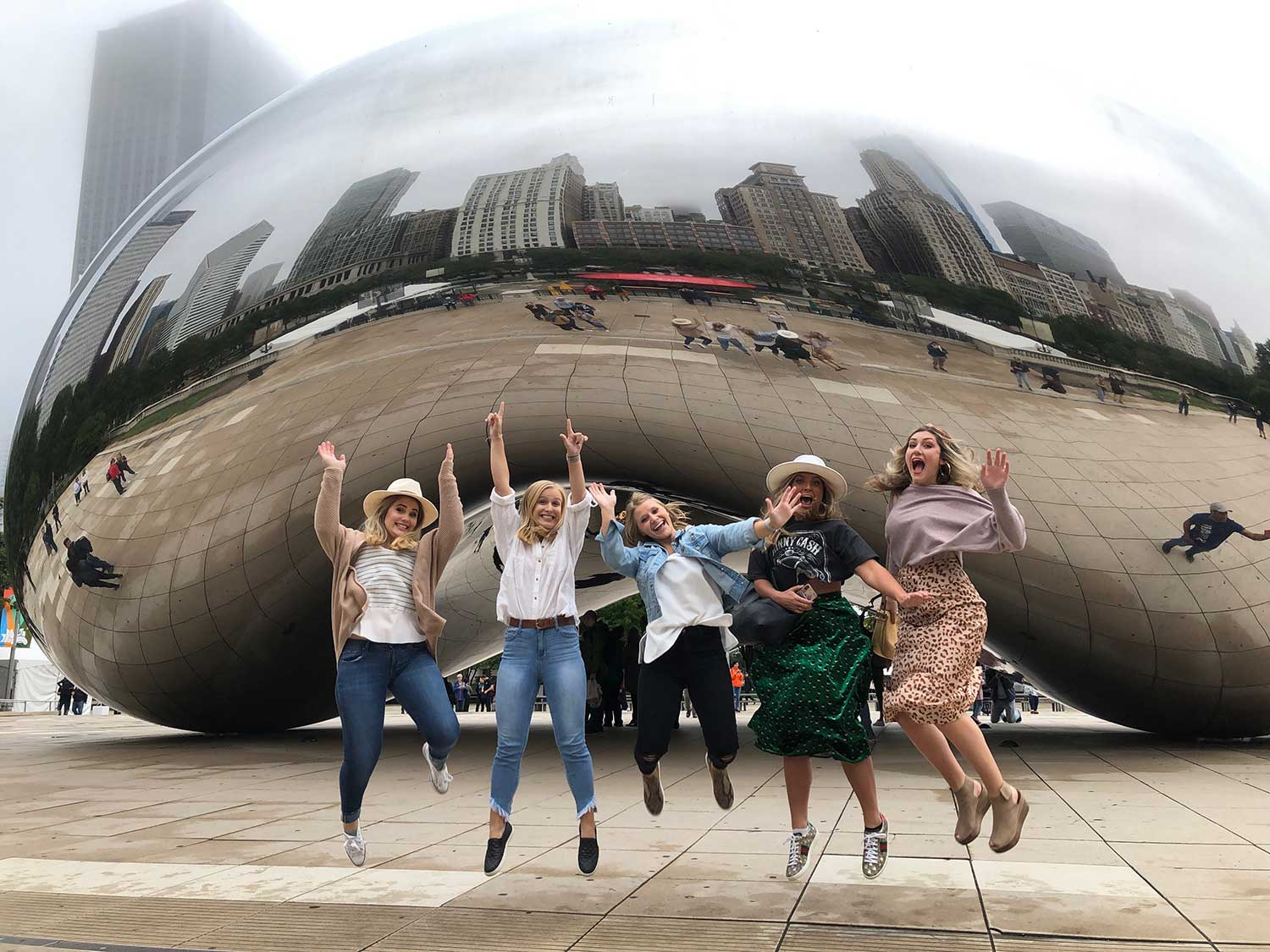 students jump/pose in front of The Bean statue in Chicago