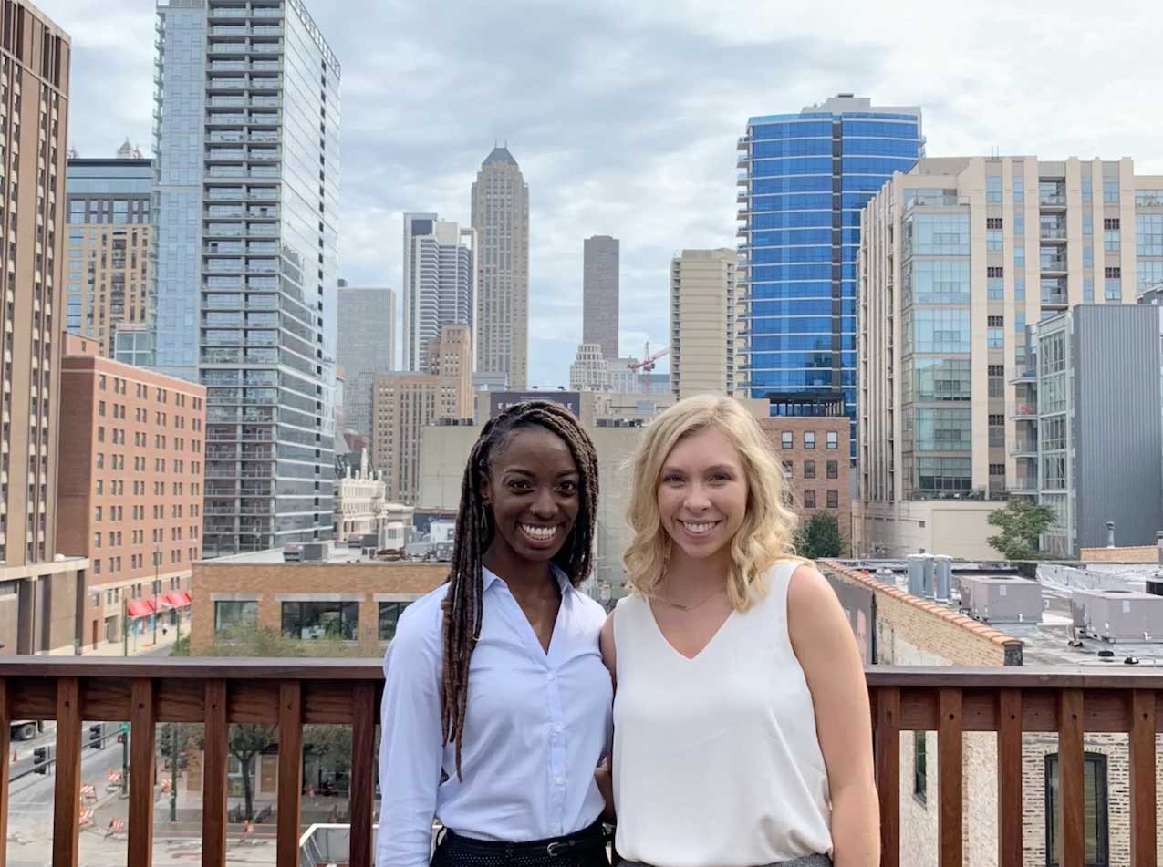two students pose in front of Chicago skyline