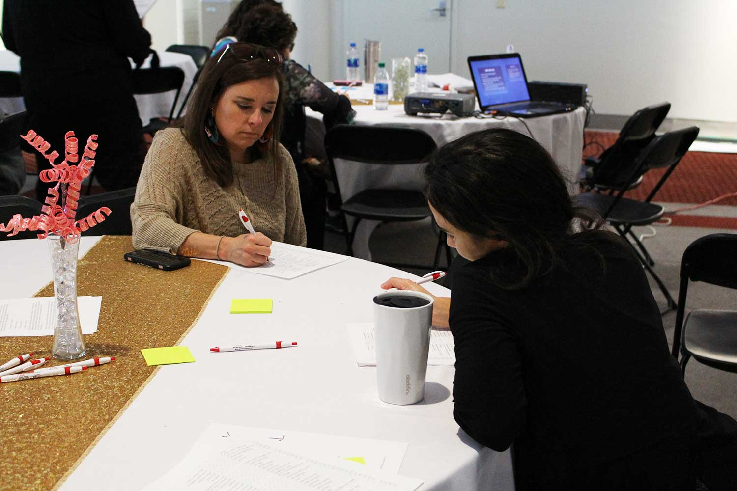 attendees work on poster project at table