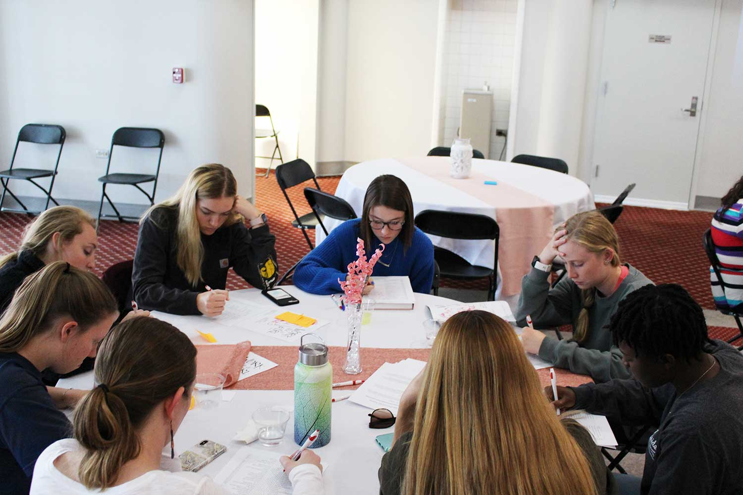 attendees at round table (8 women) work at round table with heads down, concentrating on paper with pen in hand