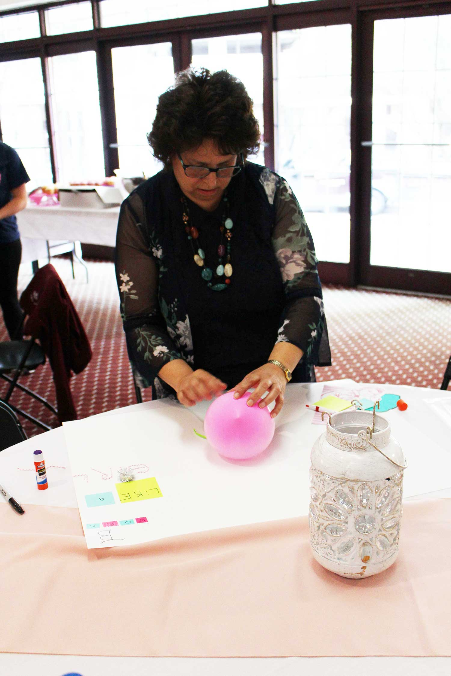 """doer"" Susan Snyder, staff, works to tape a pink balloon on her poster"