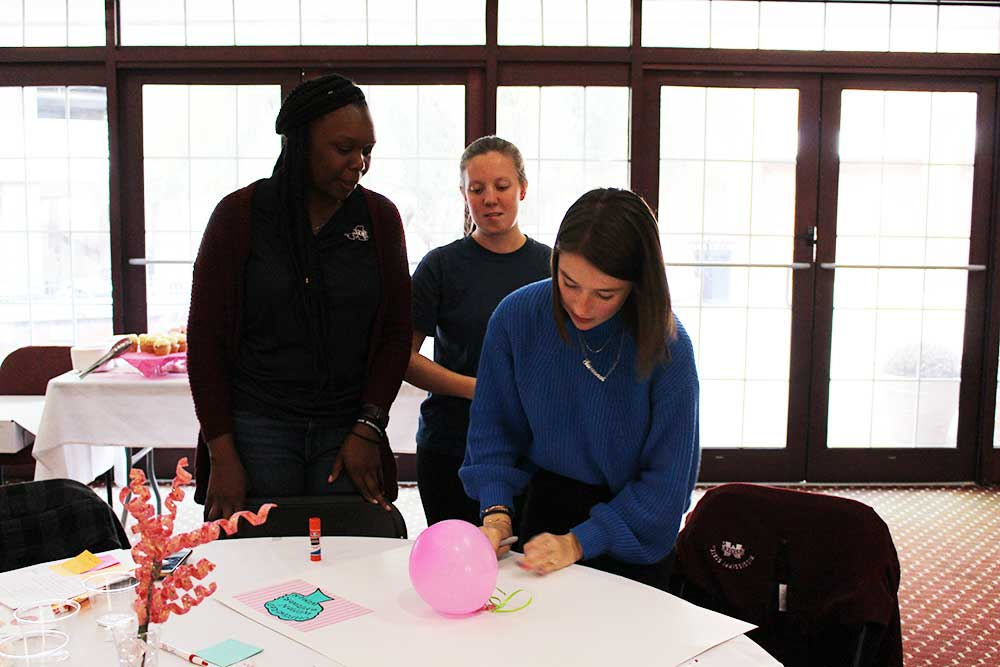 "student ""doer,"" right, works to tape a pink balloon on her poster as Jazmine Melton, left, student, and Jalyn Wallin, middle, student, look over her shoulder"