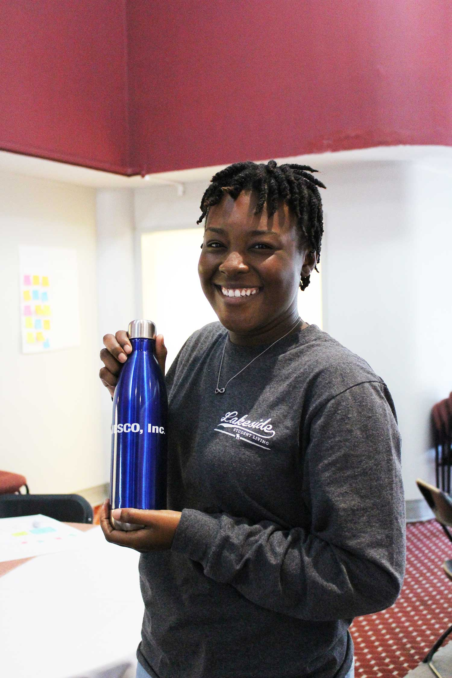 Kenya Thompson, smiling, displays blue water bottle with JESCO on it