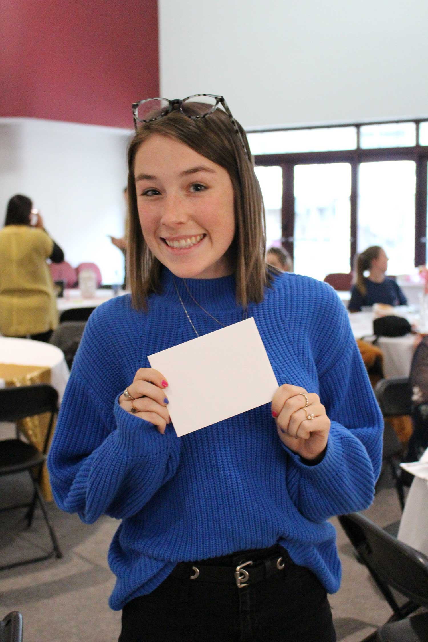 student smiles with gift card envelope in hand