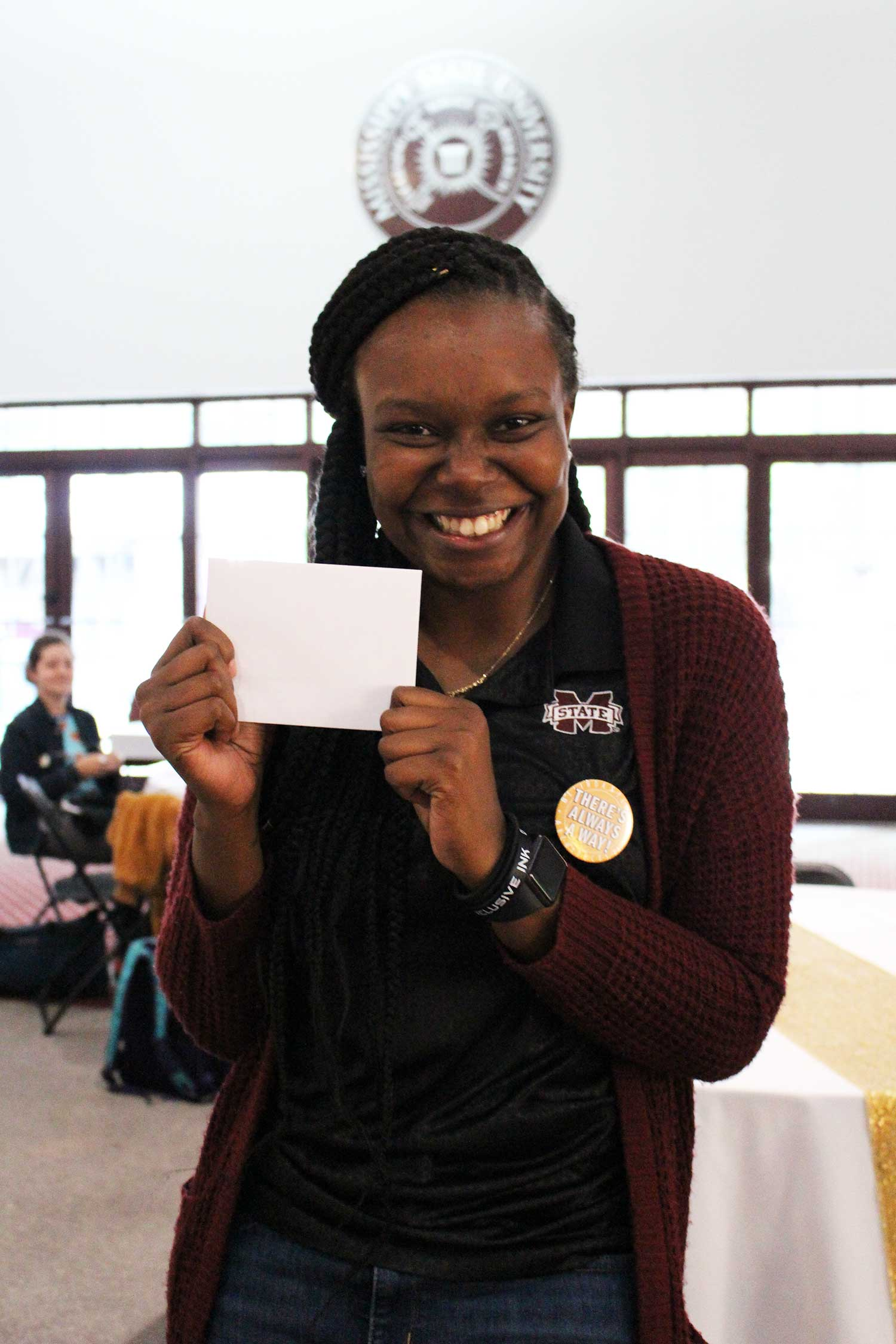 Jazmine Melton smiles with gift card envelope in hand