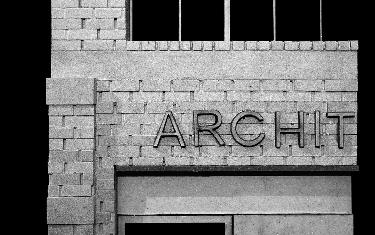 "black and white image of architecture building facade (""archit"" letters shown)"