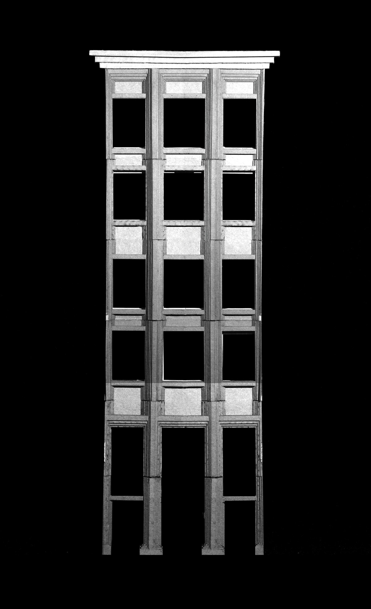 black and white image of a wooden model of a building with 12 windows (4 rows of 3)