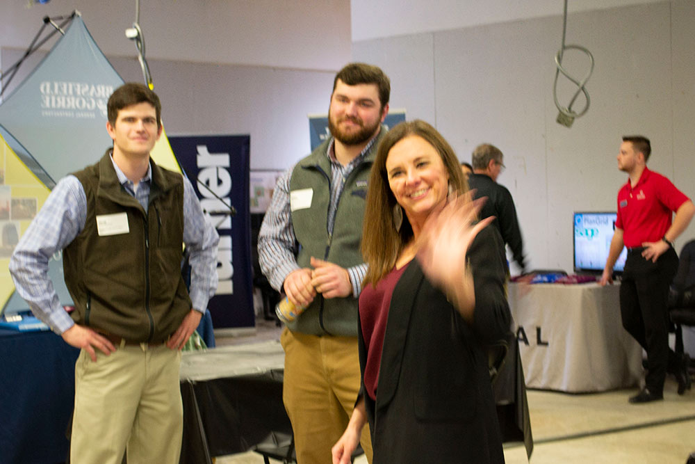 a company representative (right) waves with students behind her at the spring 2020 Building Construction Science Program career fair in Howell Building