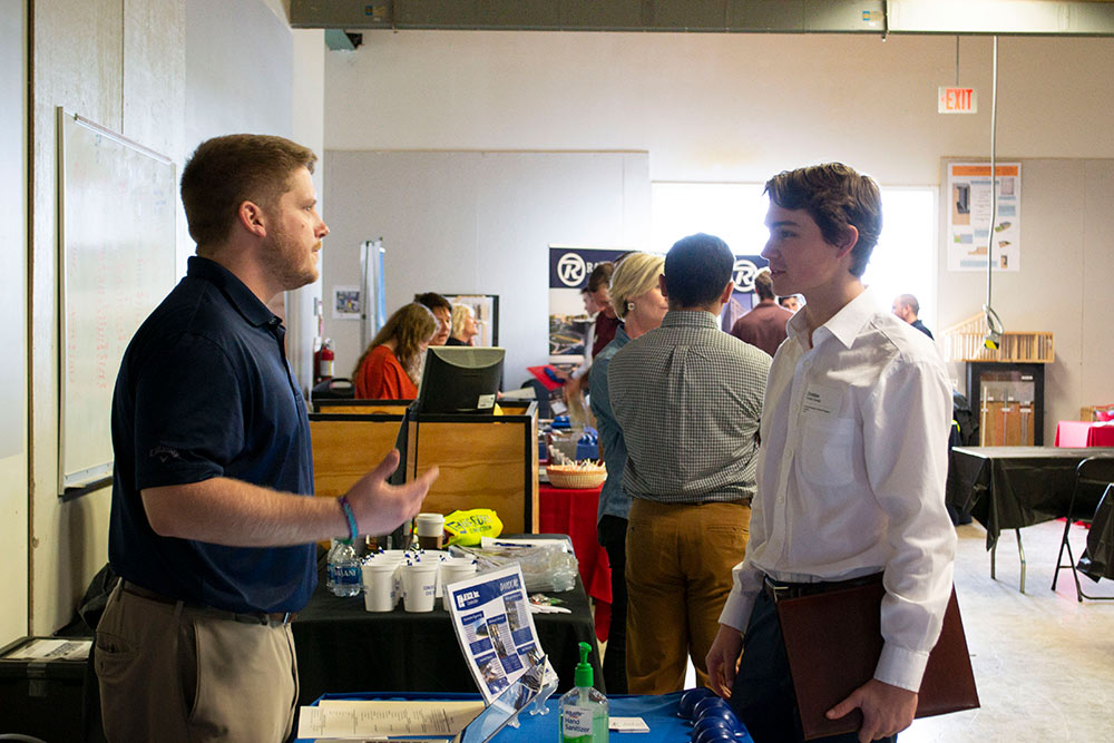 a student (right) talks with a company representative (left) at the spring 2020 Building Construction Science Program career fair in Howell Building