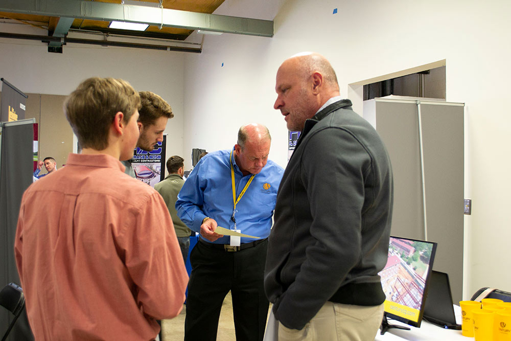 students talk with company representatives at the spring 2020 Building Construction Science Program career fair in Howell Building