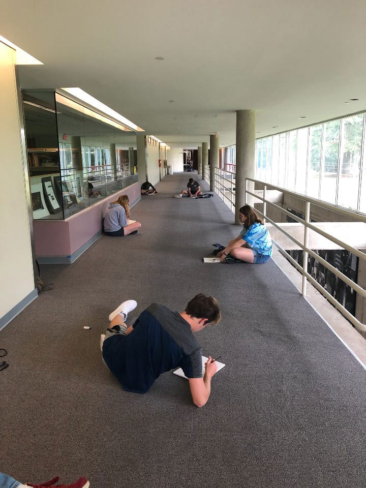 campers scattered on floor sketching in Giles hall outside of main office