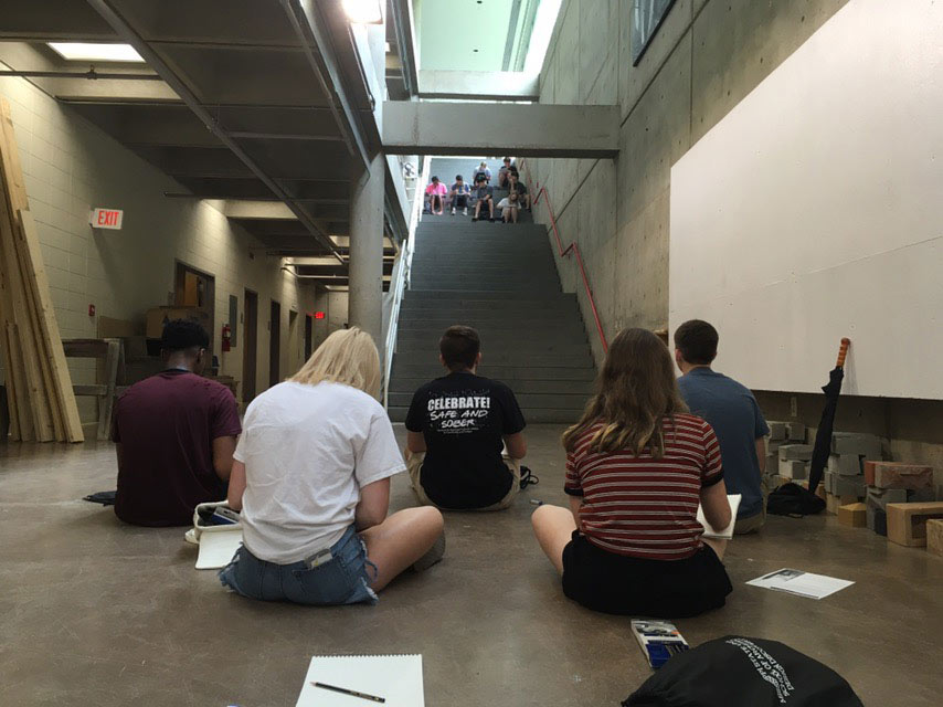 view from behind of students sketching stairwell (going up) in Giles Hall. Students can be seen sketching down (facing) at the top of the stairs as well.