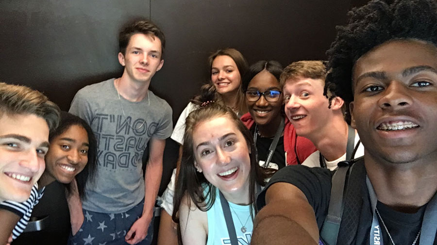a group of campers and their counselor take a selfie in an elevator