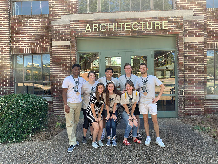 "Design Discovery 2019 architecture student counselors pose outside of Giles Hall under the ""architecture"" lettering on the building"