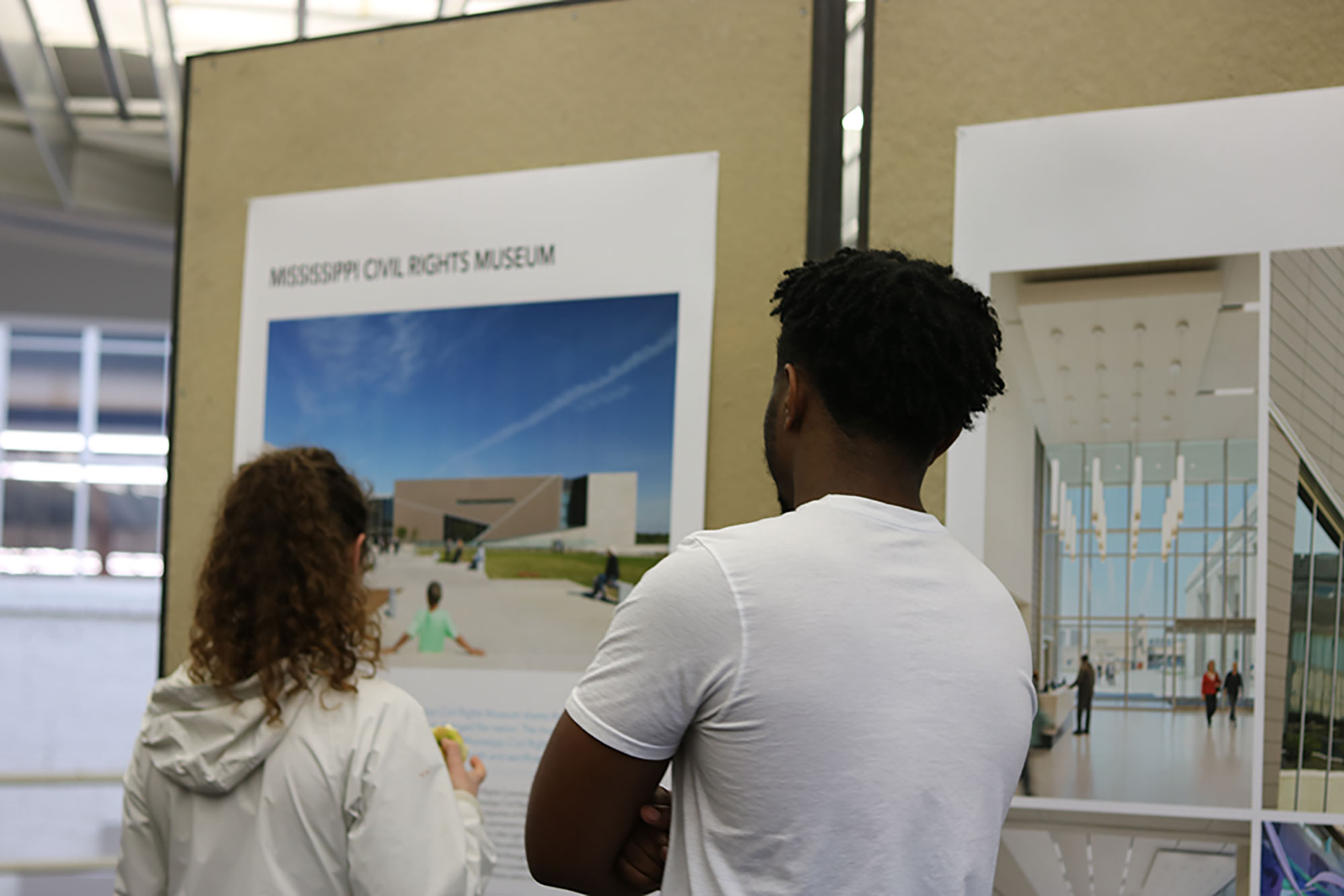 "2 students view a board in ""The Work of Philip Freelon"" exhibit during a reception in he Charlotte and Richard McNeel Gallery on the second floor of Giles Hall."