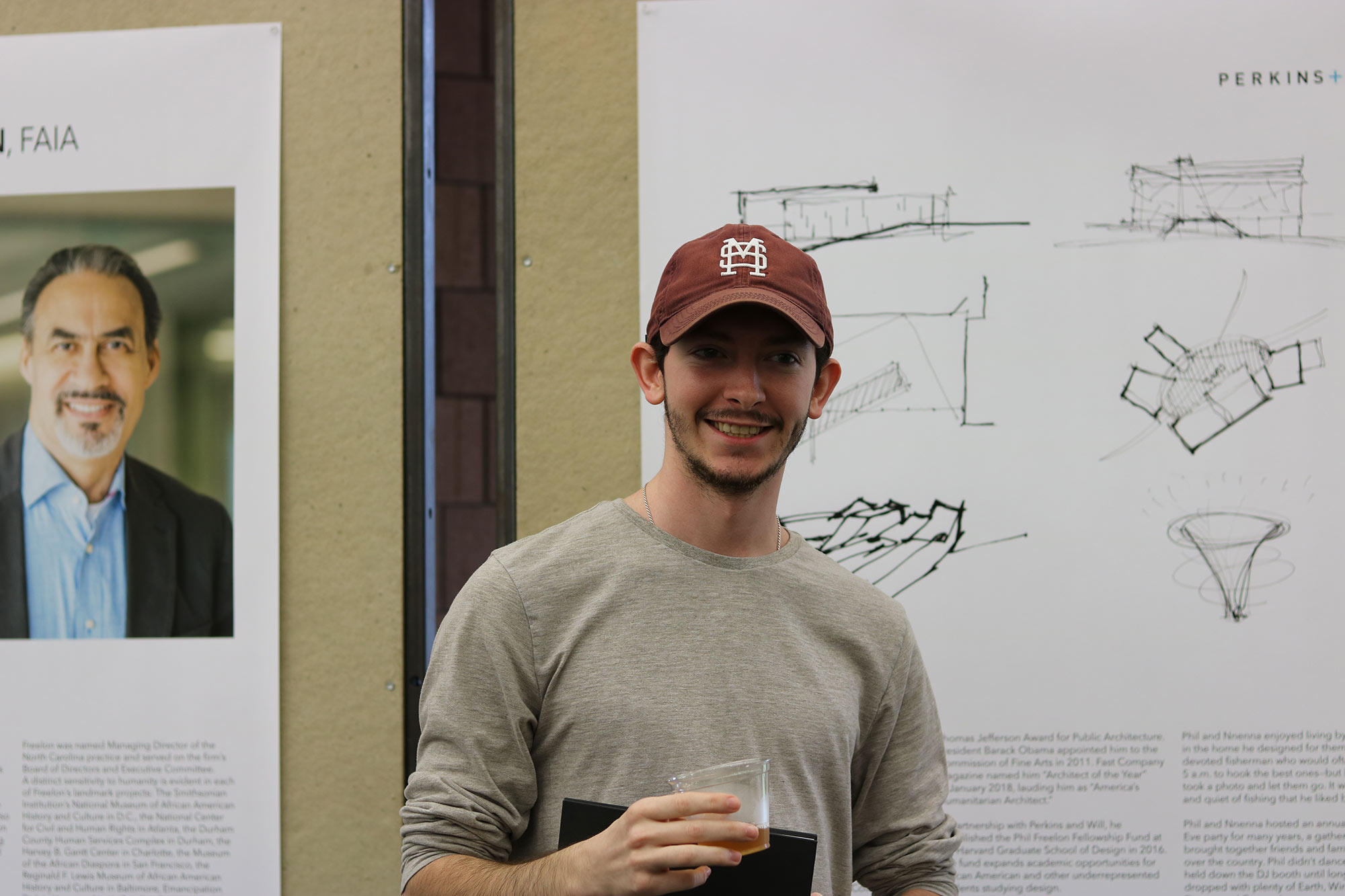 "male student poses in front of board in ""The Work of Philip Freelon"" exhibit during a reception in he Charlotte and Richard McNeel Gallery on the second floor of Giles Hall."