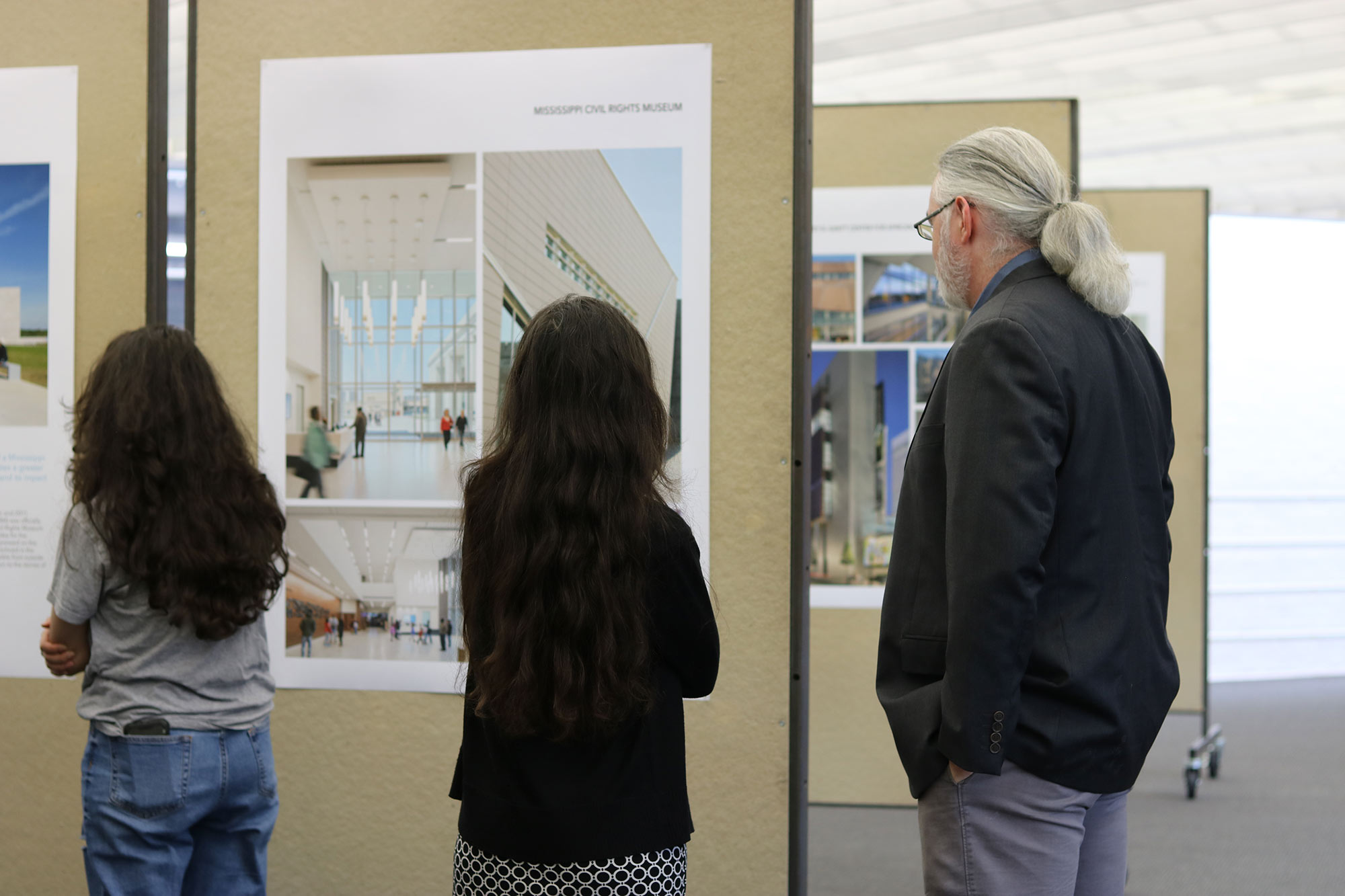 "3 guests view ""The Work of Philip Freelon"" exhibit during a reception in he Charlotte and Richard McNeel Gallery on the second floor of Giles Hall."
