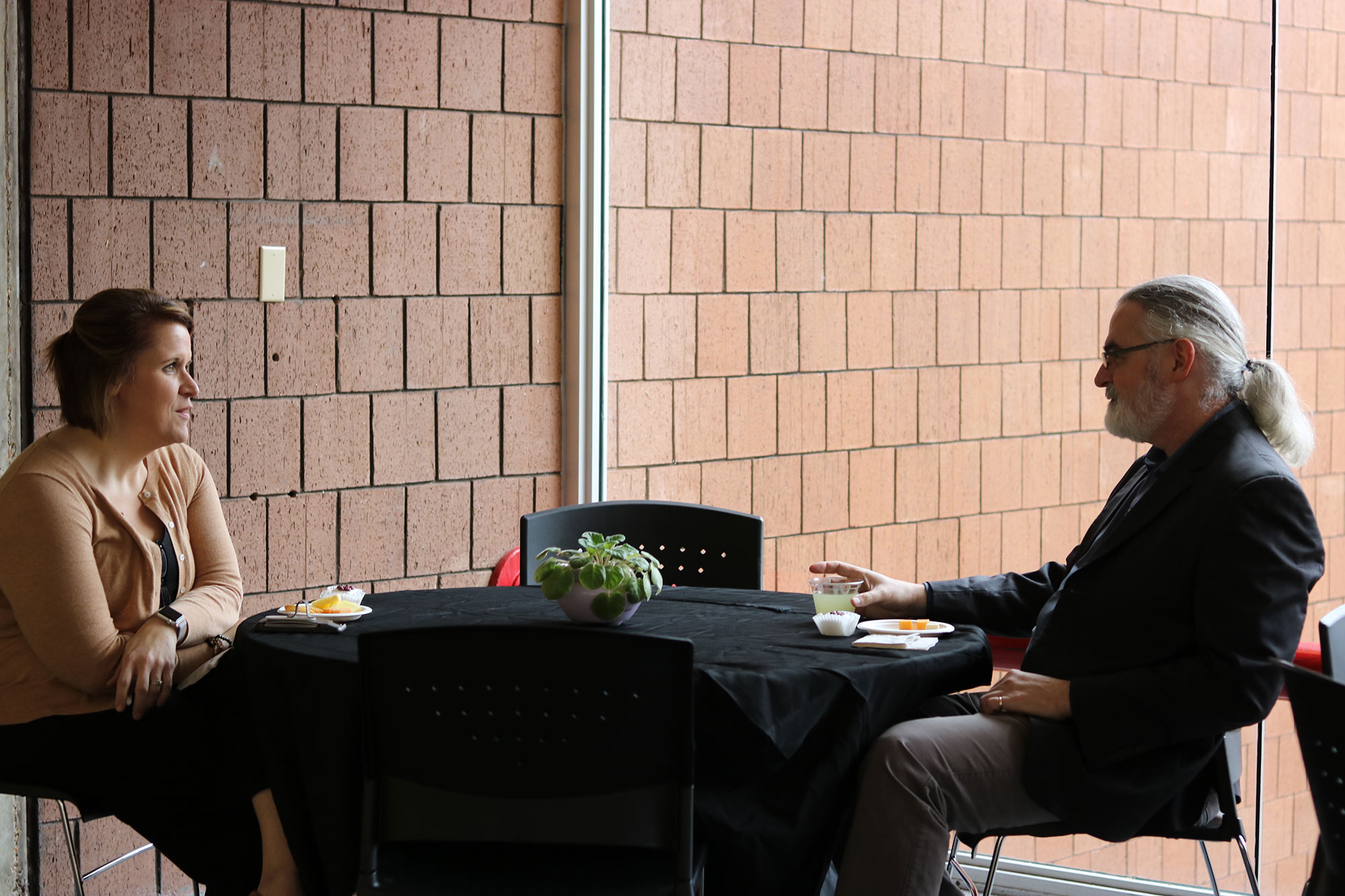"left, Laura Mitchell, sits at a table with Jassen Callender (right) outside of ""The Work of Philip Freelon"" exhibit during a reception in he Charlotte and Richard McNeel Gallery on the second floor of Giles Hall."