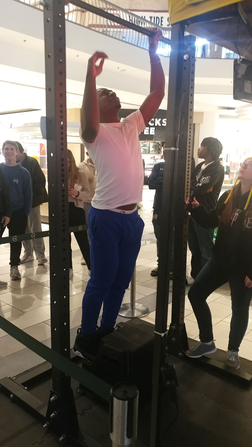 Young male attempts a pullup as others look on - appears to be in a mall