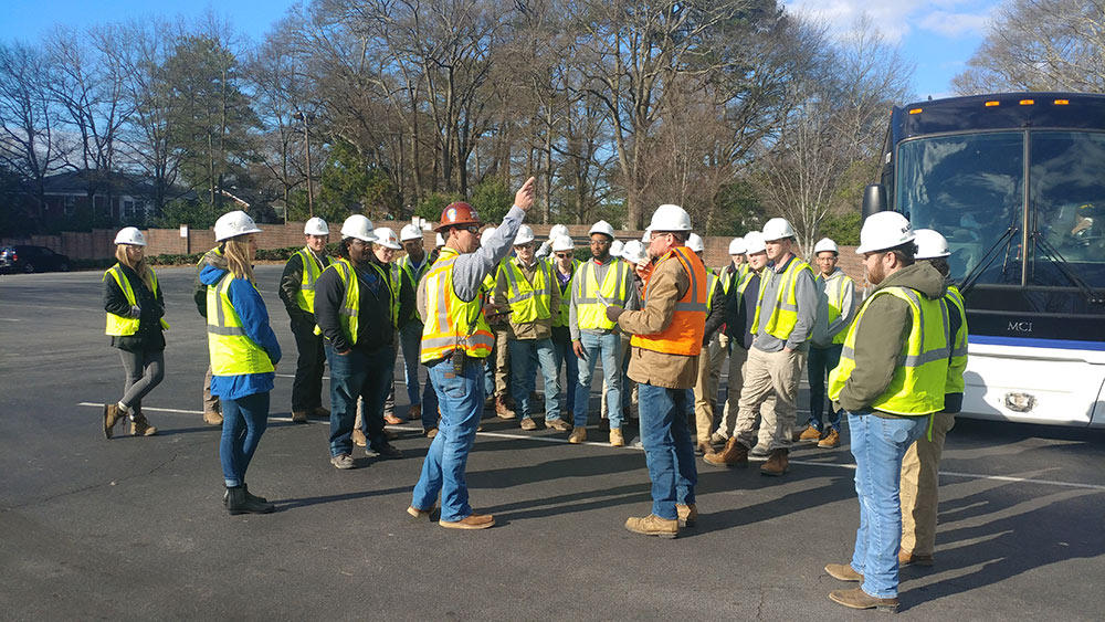 Mississippi State building construction science students gather and listen in a group to a construction professional as they arrive at a site in Atlanta - wearing safety vests and hard hats