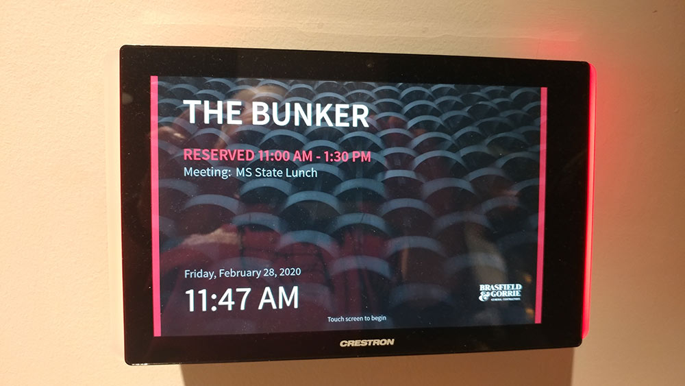 "tv screen on wall- says ""The Bunker. reserved 11 a.m. - 1:30 p.m.. Meeting: MS State Lunch"