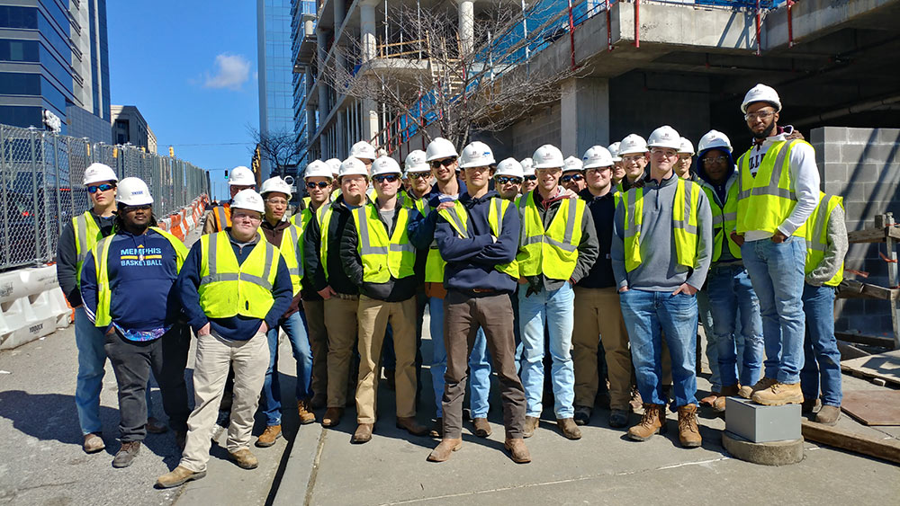 Mississippi State building construction science first-year students pose in a group in Atlanta - wearing safety vests and hard hats