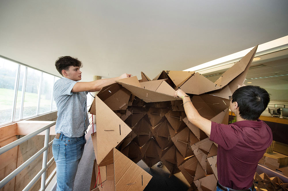 students working on cardboard structure in arch shape