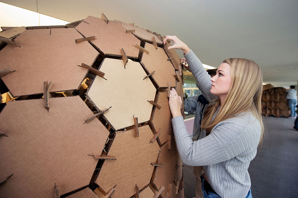 female student working on cardboard structure in arch shape