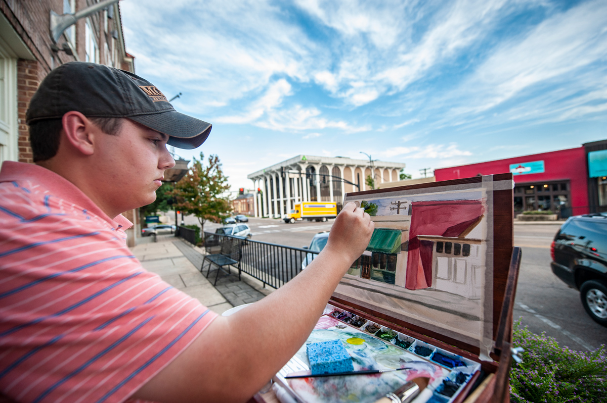 MSU Art Student Garrett Seal paints the scenes of Starkville's Main Street during his off time this summer.