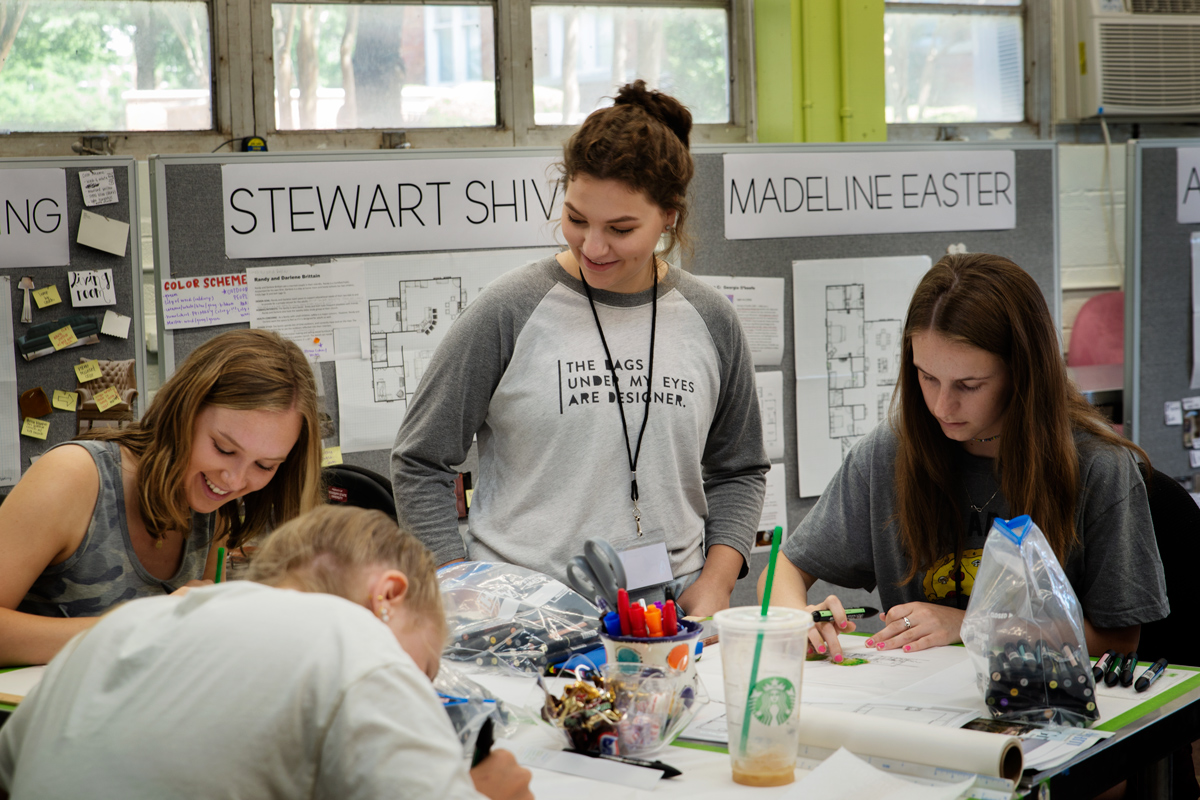 Nancy Strube and three incoming freshman sketching in an interior design studio on campus