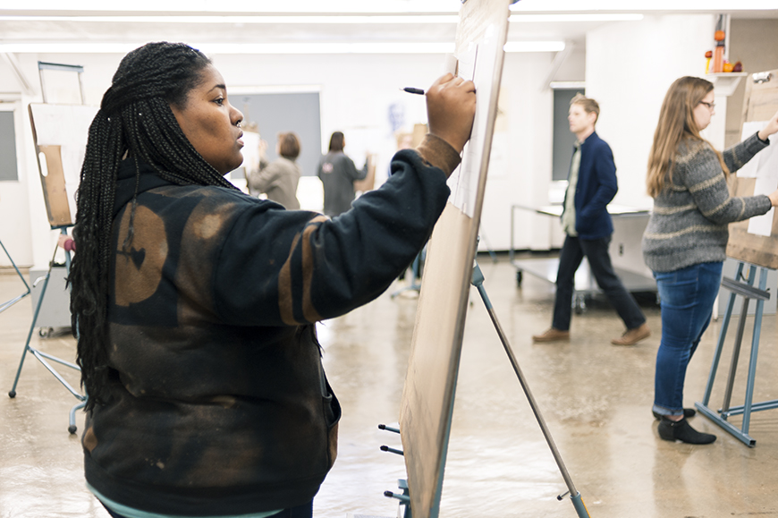 An art students draws on a canvas in a classroom.