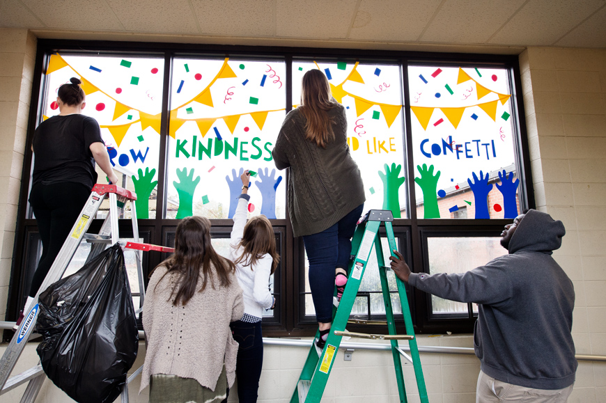 Five art students apply graphic window stickers to windows at Sudduth Elementary school as final class project and outreach.