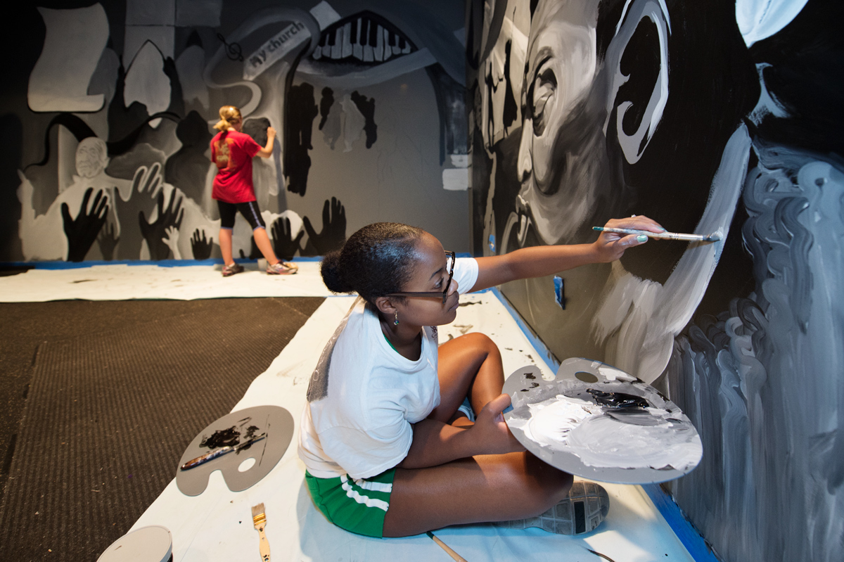 Two art students paint a music-themed mural on the walls of the Dawg House stage.