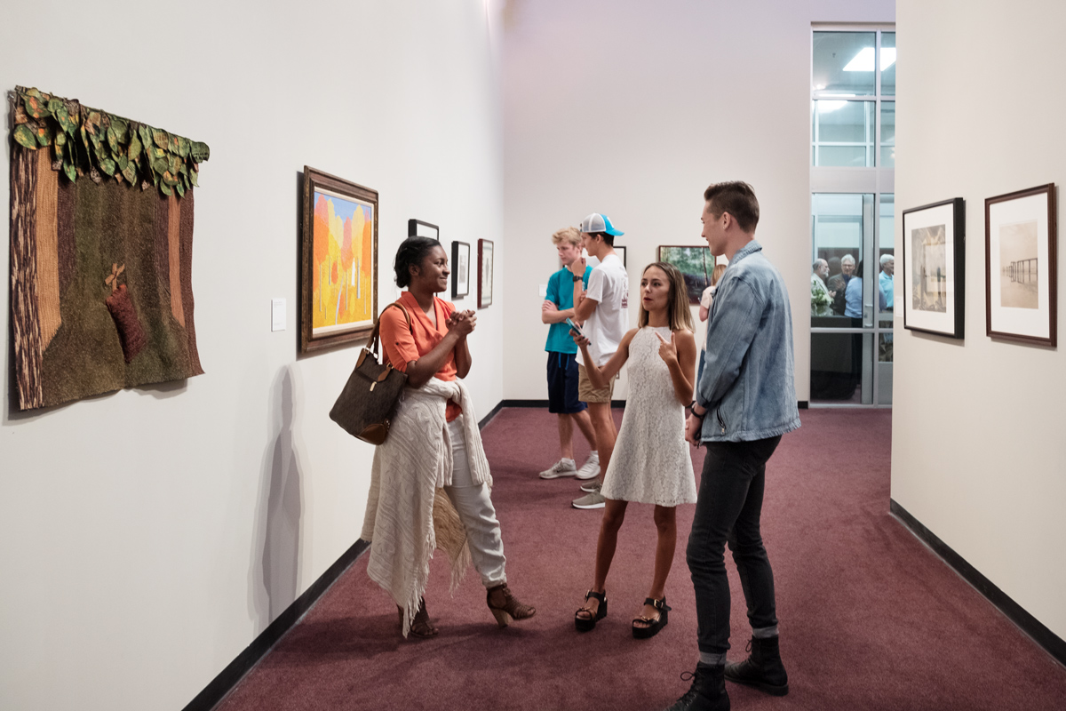 Three students chat in the Cullis Wade Depot Art Gallery, surrounded by art from the Mississippi Museum of Art's collection.