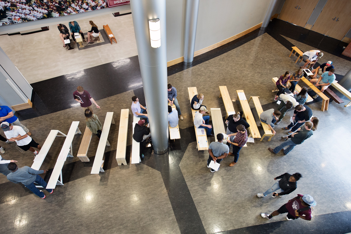 Viewed from above, dozens of benches are lined up with architecture students and professors talking and sitting amongst them.