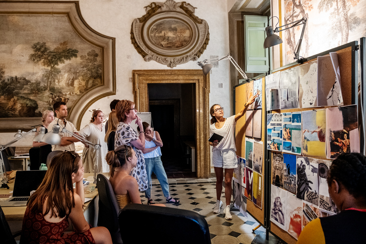 Surrounded by 16th Century decorations on the palace walls of their Rome art sttudio, CAAD students critique their poster designs. Photo by: Megan Bean July 24, 2019
