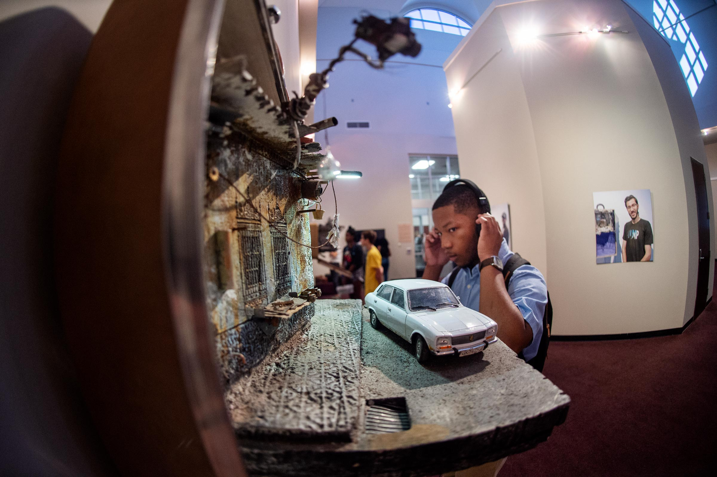 With the details of a suitcase diorama in the foreground, art major Christian Ivy listens to one of the audio clips accompanying the UNPACKED exhibition.