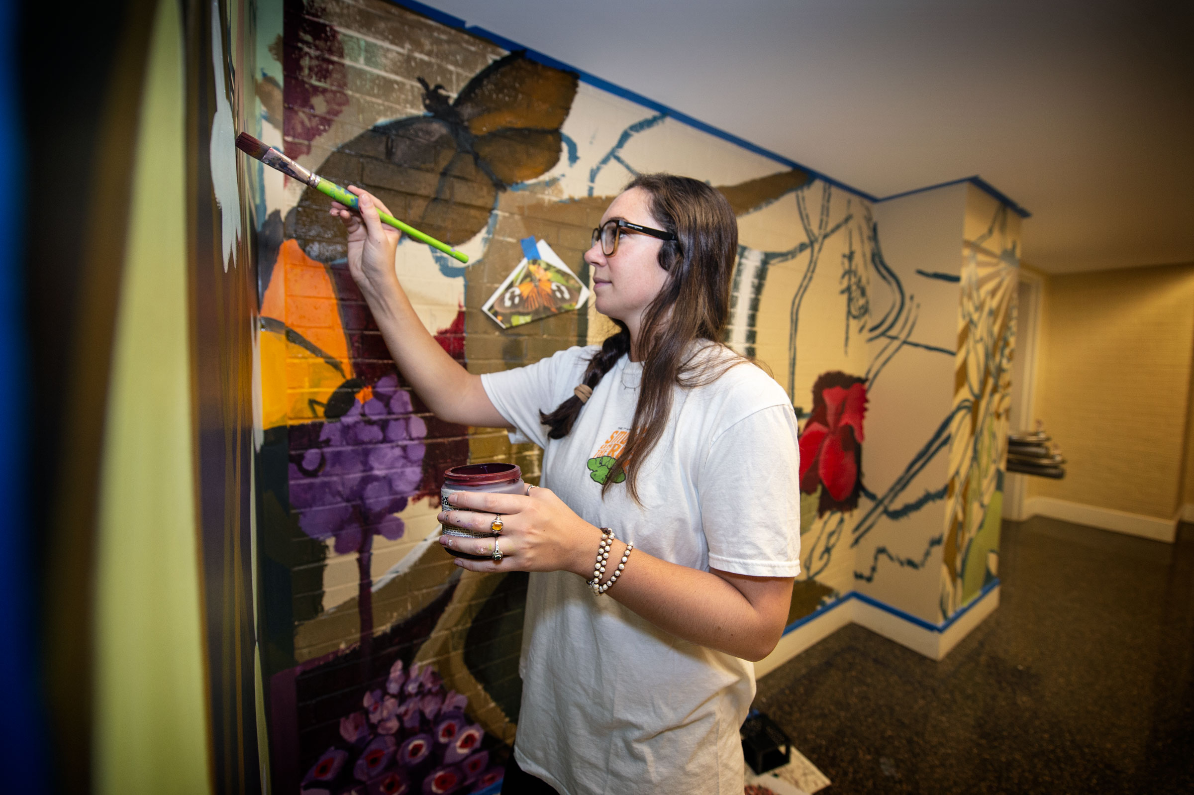 Art student Ronni Brashear paints a Harned hallway wall with butterflies and other subjects of Biological Sciences departmental research.