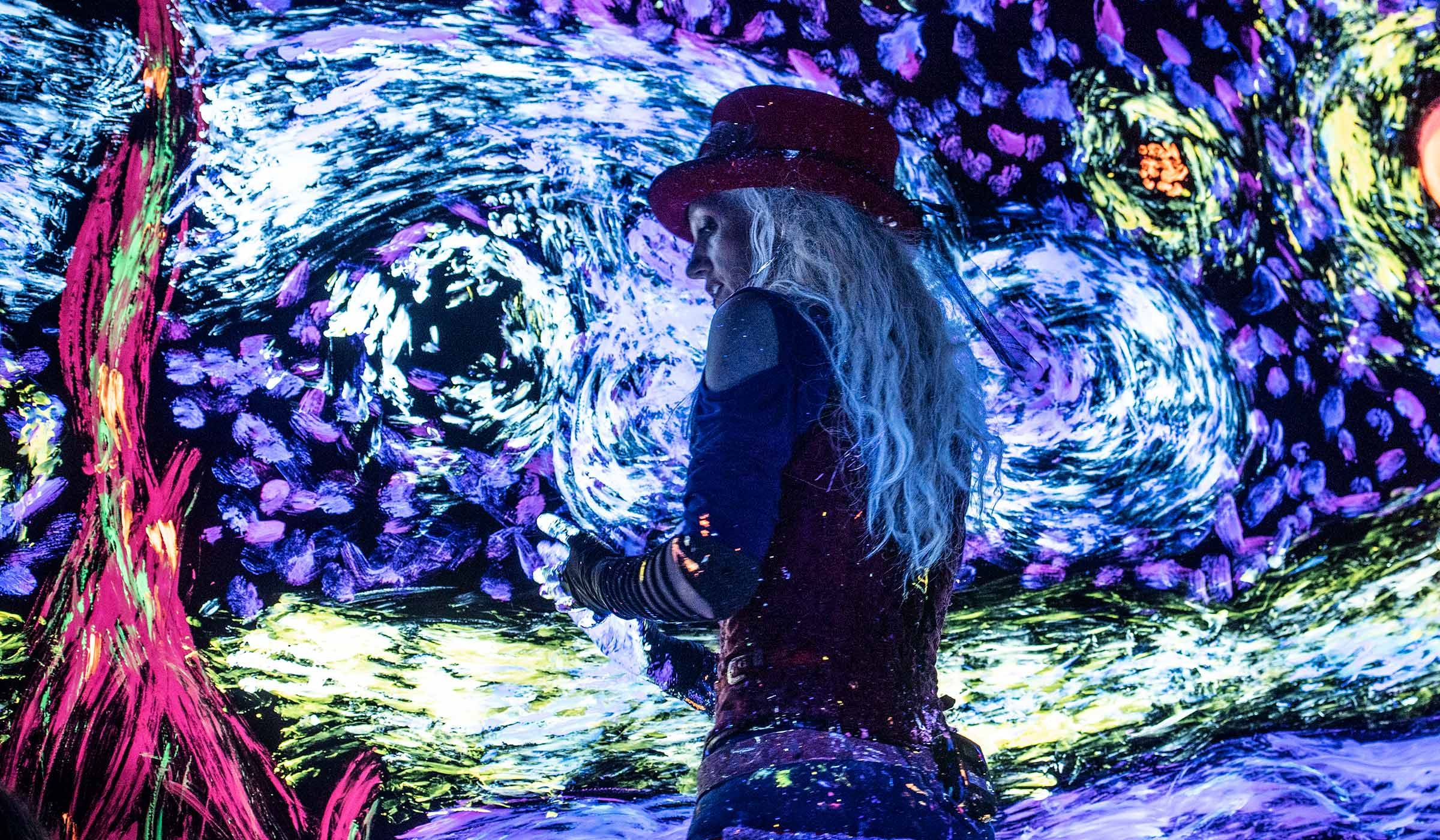 Lit by glowing blaclights, the female Artrageous lead performer uses her hands to add glowing paint to a canvas covered with a a swirly sky painting.