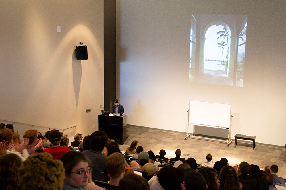a view from the back of the Robert and Freda Harrison Auditorium in Giles Hall with a presenter at the lectern